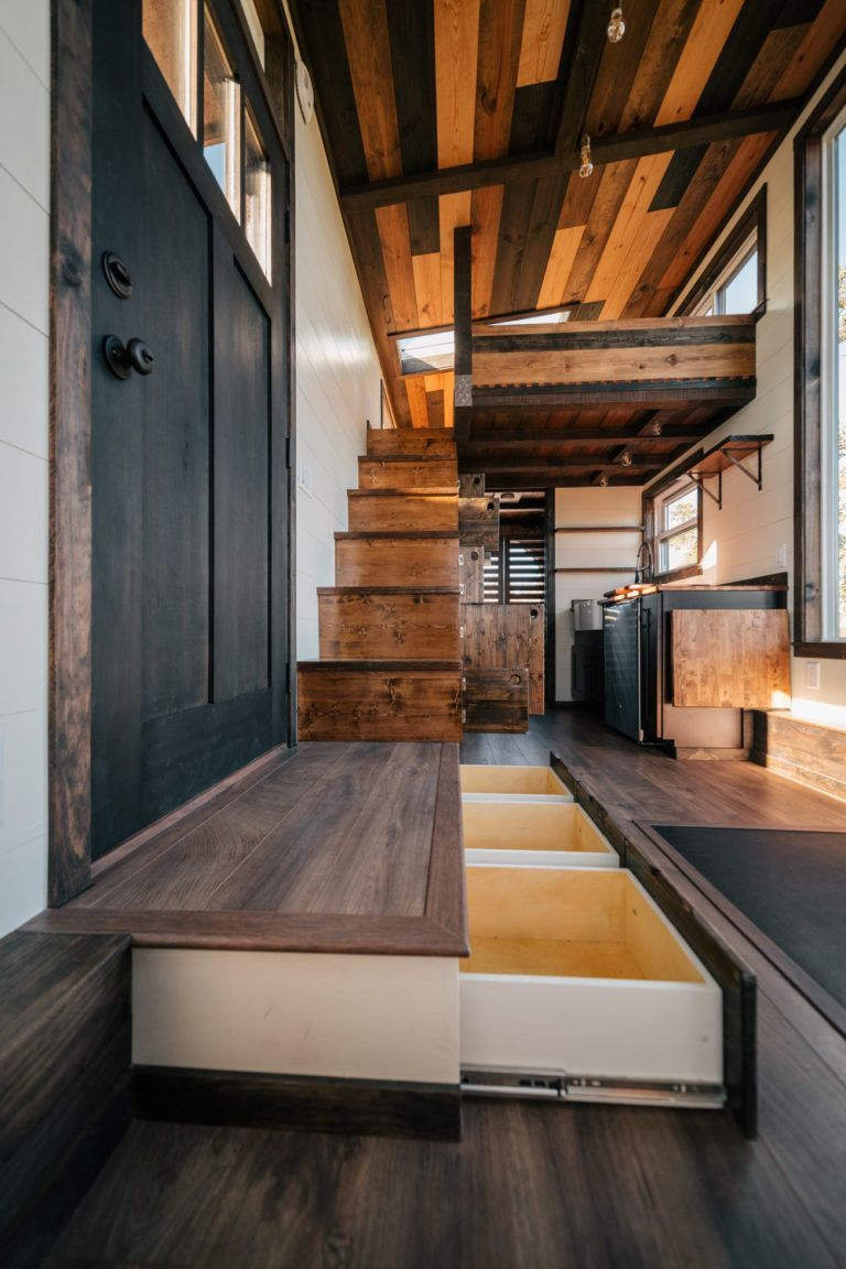 The Silhouette: 26ft Tiny House on Wheels with Large Windows and a Built-in Gym! #tinyhome Such practical storage ideas - the floor/step drawers, under stairs cabinets, and fold down counter <3 #tinyhousestorage