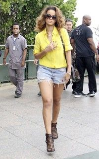 Rhianna wearing Prada sunglasses, yellow blouse, cut-off Levi shorts and Givenchy booties.