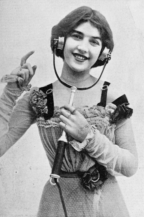 A young woman wearing an electrophone with which she could listen to live entertainment such as plays and concerts over the telephone line, 1901. By Foulsham and Banfield.