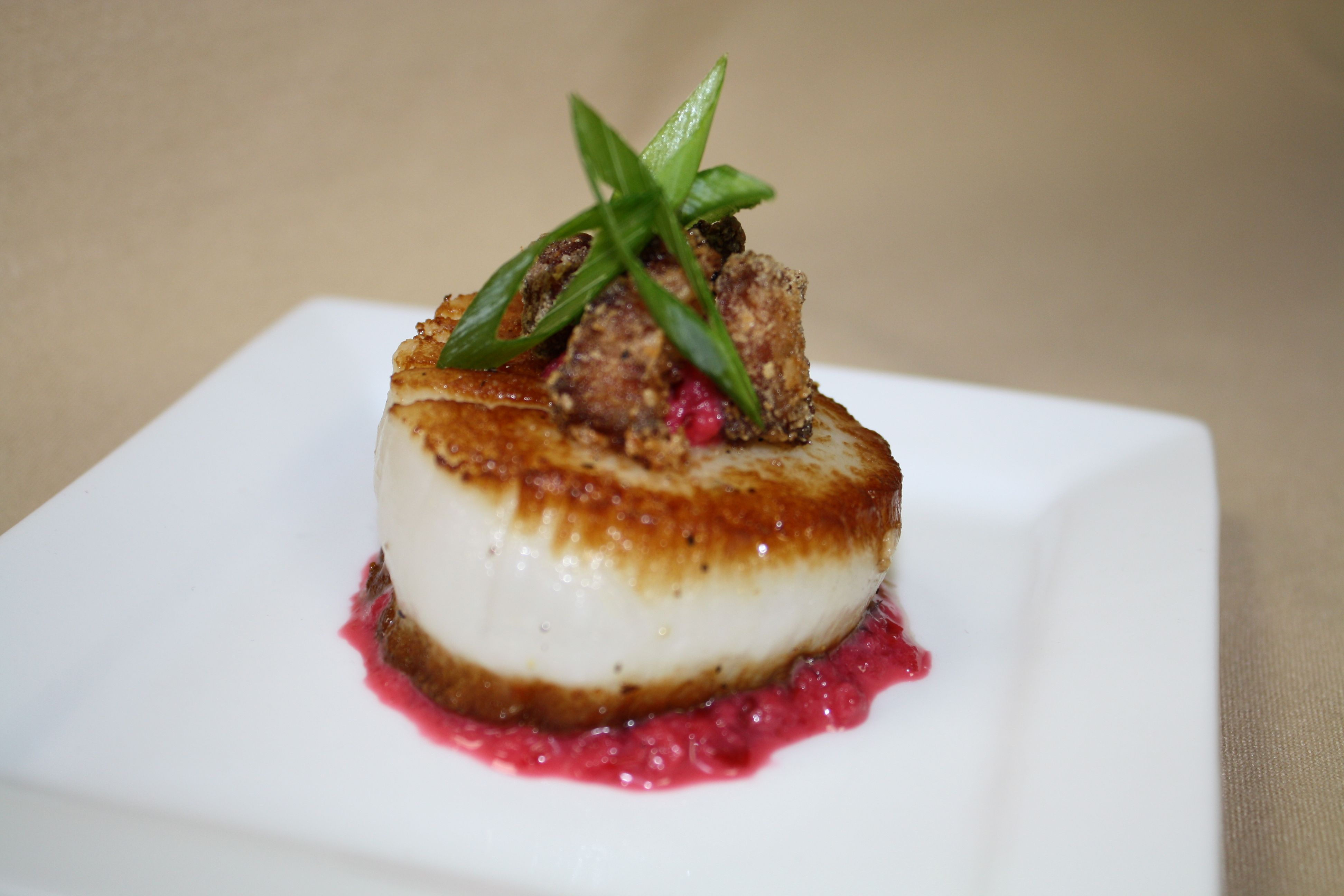 Pan Seared Sashimi Grade Sea Scallops in a pool of orange cranberry puree, topped with fried pork belly and green onions.