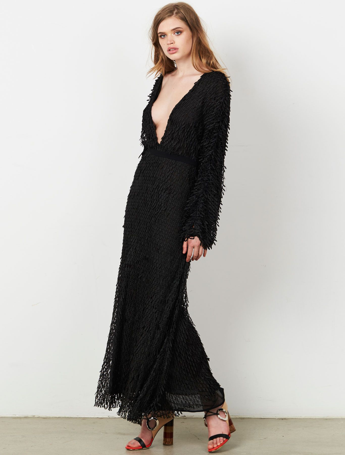 BADLANDS L/S MAXI DRESS With a sense of timeless modernity, this breathtaking black maxi dress has been designed from a unique 3D lace fabrication to give the illusion of being adorned with hundreds of delicate ruffled feathers. With a flattering plunge neck and back line, balanced by billowing long sleeves, the dress uses a series of fine ties to temper the over-sized silhouette. Available www.steviemay.com.au