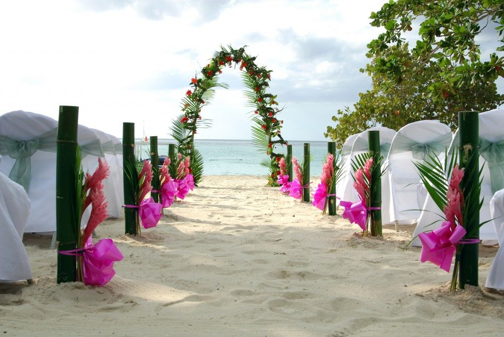 Charming bamboo wedding arch in a beach with pink ribbons and sand charming bamboo wedding arch in a beach with pink ribbons and sand flooring seasonal beautiful junglespirit Gallery