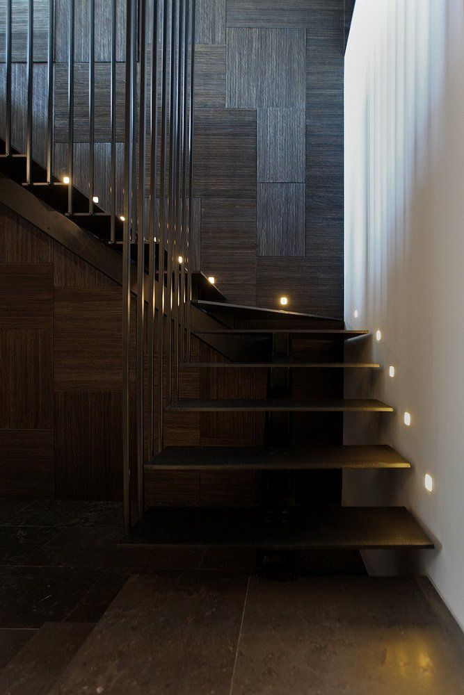 Dark and moody interior with metal staircase and built in lighting