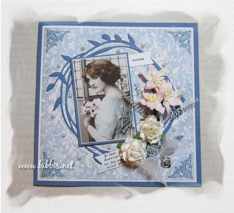 Fødselsdagskort i blå kartong og mønsterpapir fra Papirdesign. Pyntet med blomster, bånd, perler, charms, snurredingser og et vintagebild...