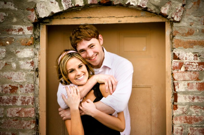 engagement portraits by door wedding couple cute pose infront of