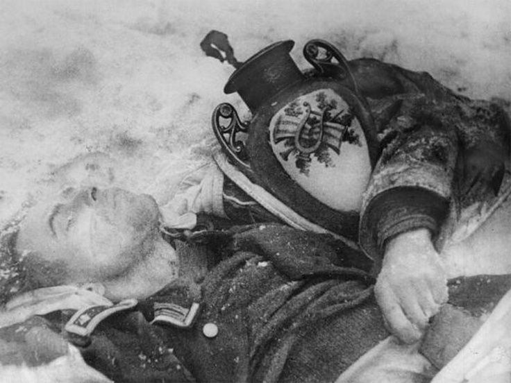 """Death and loot: This German junior lieutenant died and froze embracing a little """"gift"""" he had collected from who knows what Russian source. The photo was taken in January 1942 in the environs of Moscow."""