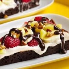 Banana Split Brownie Pizza 1 (19 1/2 ounce) package brownie mix 1 (8 ounce) package cream cheese, softened 1 (8 ounce) can crushed pineapple, drained 2 tablespoons sugar 1/2 cup nuts strawberry banana chocolate syrup Directions: 1 Preheat oven to 375. 2 Prepare brownie mix according to package directions. 3 Place parchment paper on 15-inch baking stone. 4 Pour brownie mixture on paper and spread into 14-inch circle. 5 Do not bake without parchment paper or batter will run off stone while…