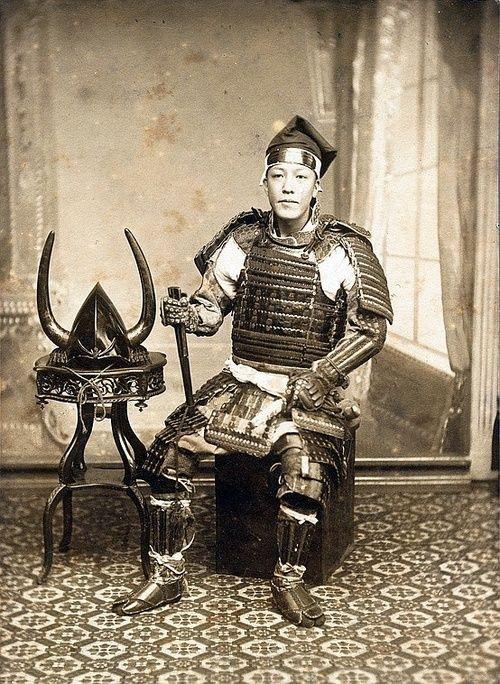 tofuist:  Samurai wearing full armor including kokake (armored foot coverings) and holding tessen fan, on his head he has an eboshi cap.