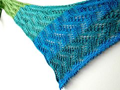 "This asymmetrical triangle shawl is built on a ""waves of wheat"" pattern repeat and knits up in a single 100g skein of sport weight yarn. Knit it up in a color-change yarn (as pictured), with mini-skeins and leftovers, or in a solid or tonal!"
