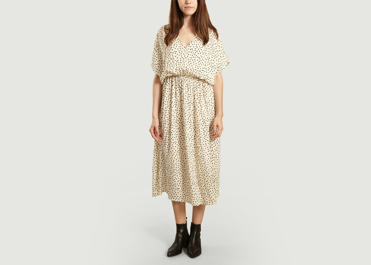 Dress in viscose with polka dots, ecru and black, short sleeves, elasticated fitted waist, V neckline, midi length, tone-on-tone finishes, flowing straight cut. The Andina dress, with its feminine and delicate print, will seduce you for its cut and the softness of its viscose. Its straight and long cut allows you to wear it on holiday as well as at the office, with heels or sneakers according to your desires.