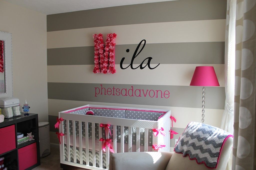 adorable nursery idea - black, grey, and pink color scheme, thick horizontal striped accent wall, name in cursive with first letter hung, and cute pink and black cloth bin shelves.