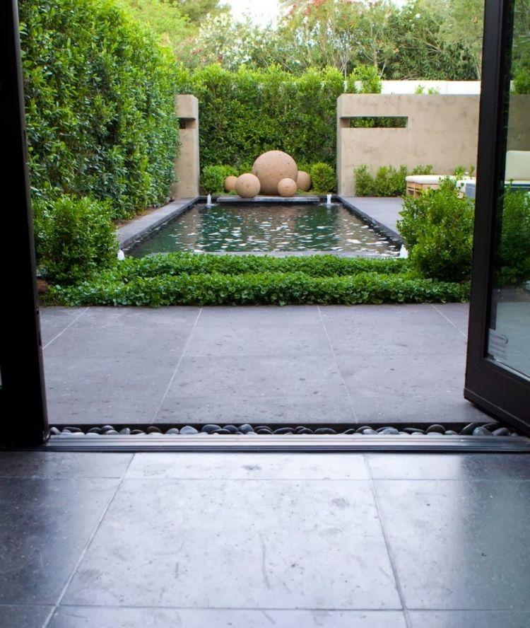 moderner Garten mit Teich, Skulpturen und Sichtschutz aus Hecke - sichtschutz im garten modern