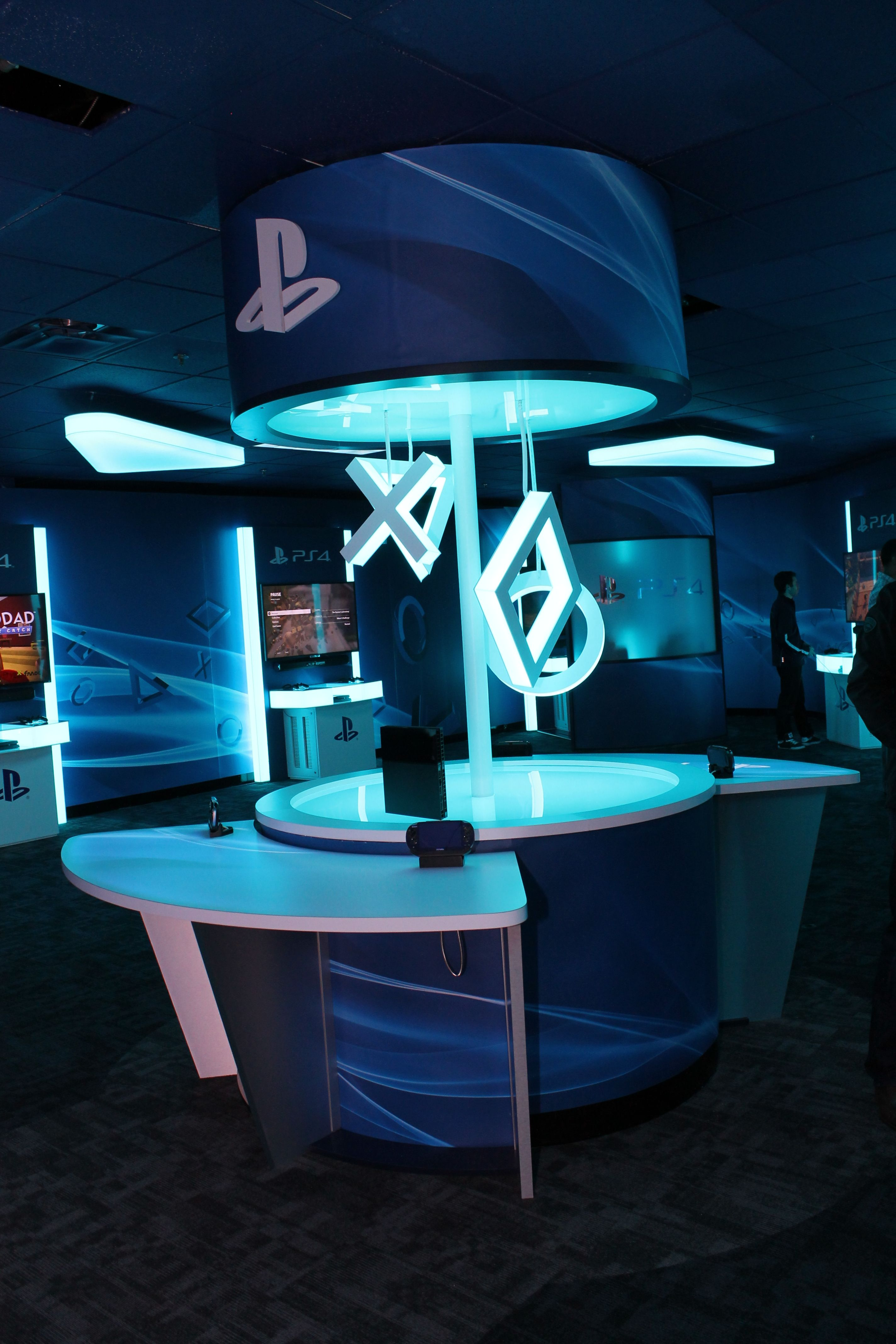 Focal Point Of The Ps4 Store Is The Hero Station With Edge Lit Hanging Symbols Game Cafe Exhibition Booth Design Boutique Interior
