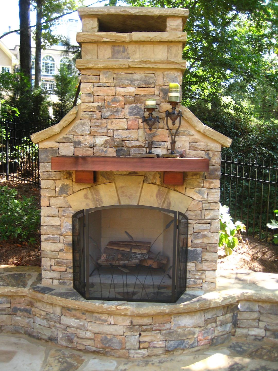 Outdoor Fireplace With Wood Mantel And Seating Wall Outdoor