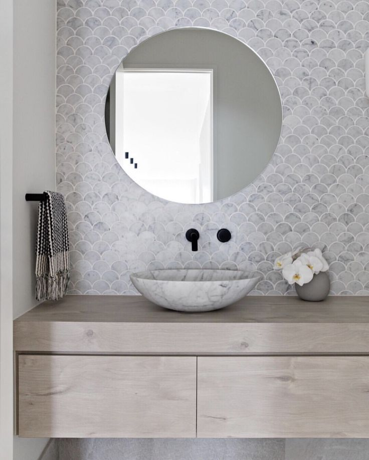 Bathroom with fish scale tiles oak vanity Carrara marble bowl round mirror and black wall  Bathroom with fish scale tiles oak vanity Carrara marble bowl round mirror and...