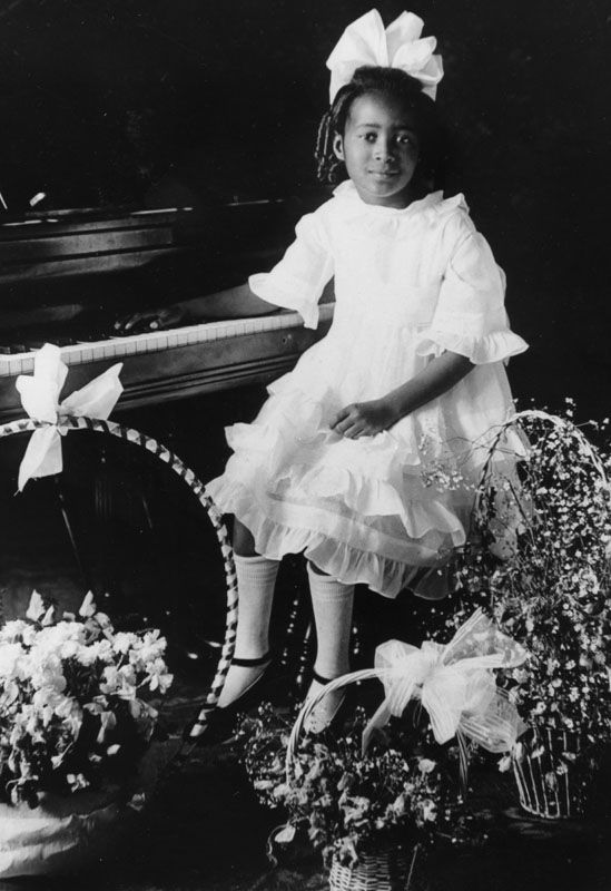Juanita, age 7, at her piano recital, surrounded by baskets of flowers, 1919 Shades of L.A.: African American Community, Los Angeles Public Library