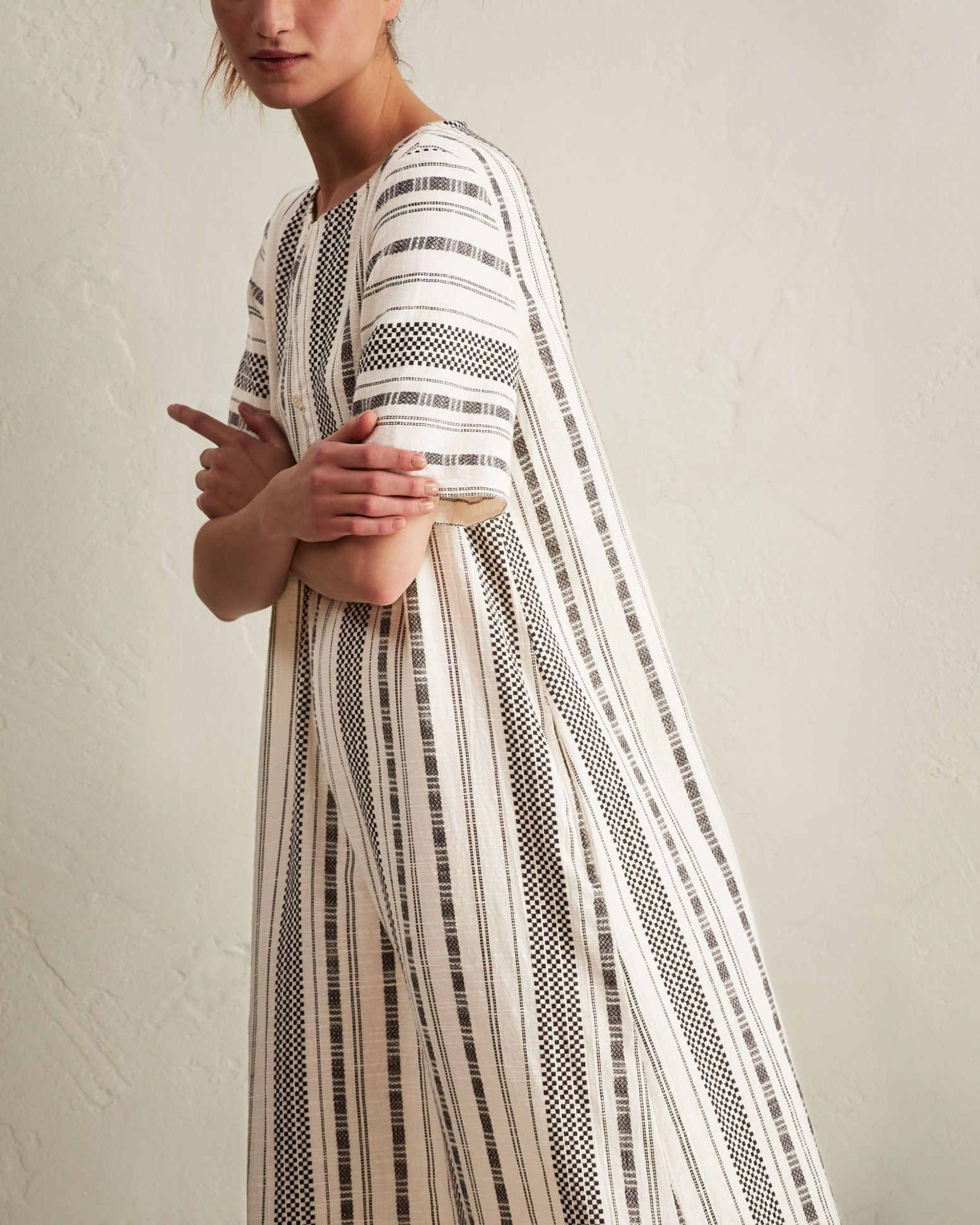 STRIPE COTTON DOBBY DISHDASHA | Weighty cotton with a stripe and chequerboard weave. Asymmetric opening fastening with button and tassel. Pockets.