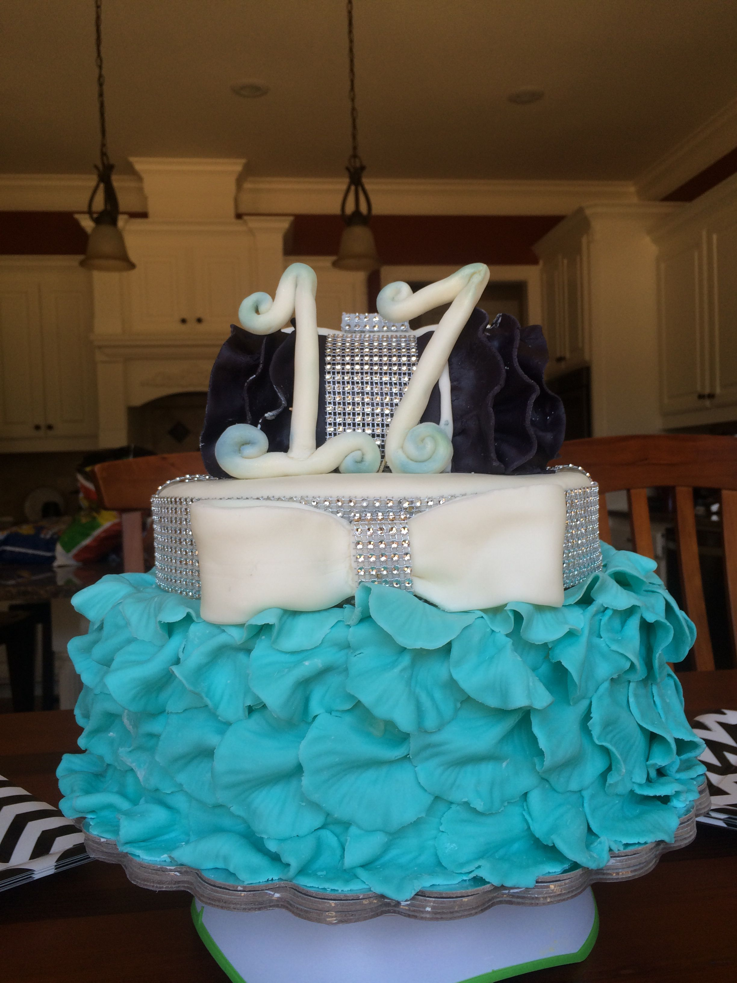 Birthday Cake with little black purse, a lot of bling and its own skirt of petals.