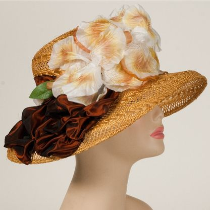 Amy is a charming derby hat designed by Louise Green. The lacy sisal hat a dark ribbon around the crown that gathers to the side. Large vintage flowers adorn the front side of the crown.