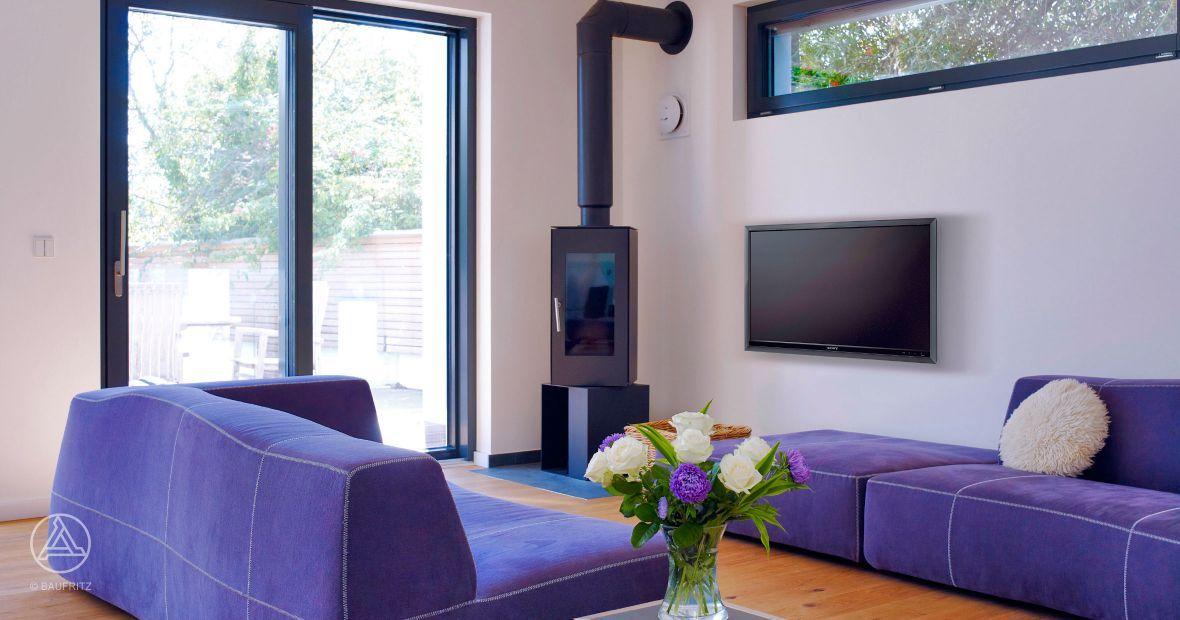 Im Wohnzimmer werden farbige Akzente durch ein lilanes Sofa - grose fenster wohnzimmer