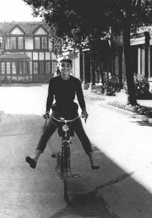 Audrey Hepburn riding a bicycle on the Paramount lot, in front of my old office building.