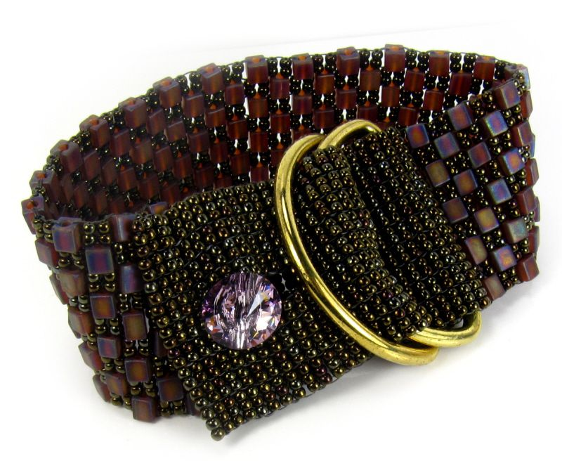 We have created this stunning statement cuff bracelet using Japanese Miyuki Glass Beads in an aubergine shade of purple with light rainbow matt finish.  The bracelet has been woven by hand and is finished with a Light Vitrail Swarovski Crystal button and gold tone buckle rings.  This bracelet will comfortably fit a 7.5 inch (19cm) wrist and is 3.3cm in width.