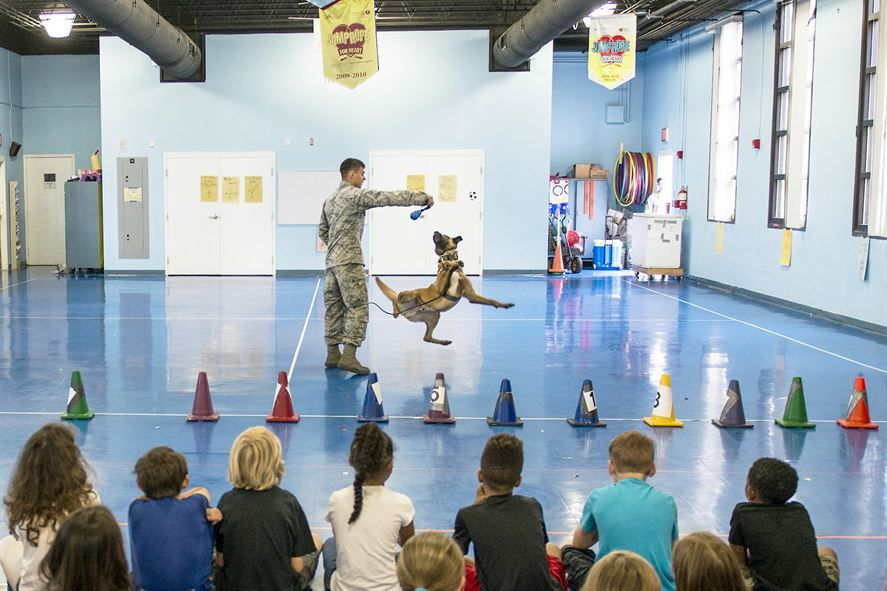 Air Force Senior Airman Chase Shankle gives a demonstration with Arko, a military working dog, for Eglin Elementary School students at Eglin Air Force Base, Fla., May 17, 2016. More than 100 children watched two military working dog teams perform during the event. Air Force photo by Samuel King Jr.