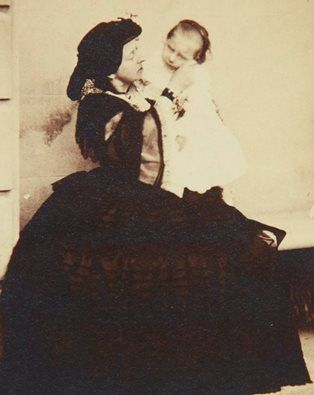 Queen Victoria holding her youngest child HRH The Princess Beatrice Mary Victoria Feodore of the United Kingdom. Circa 1869