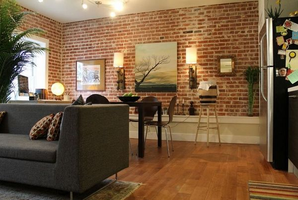 exposed brick wall in living rooms loft style design ideas wood flooring black sofa wall sconces