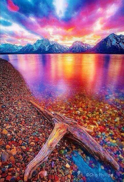 Snow covered mountains &  rocks of color on shore