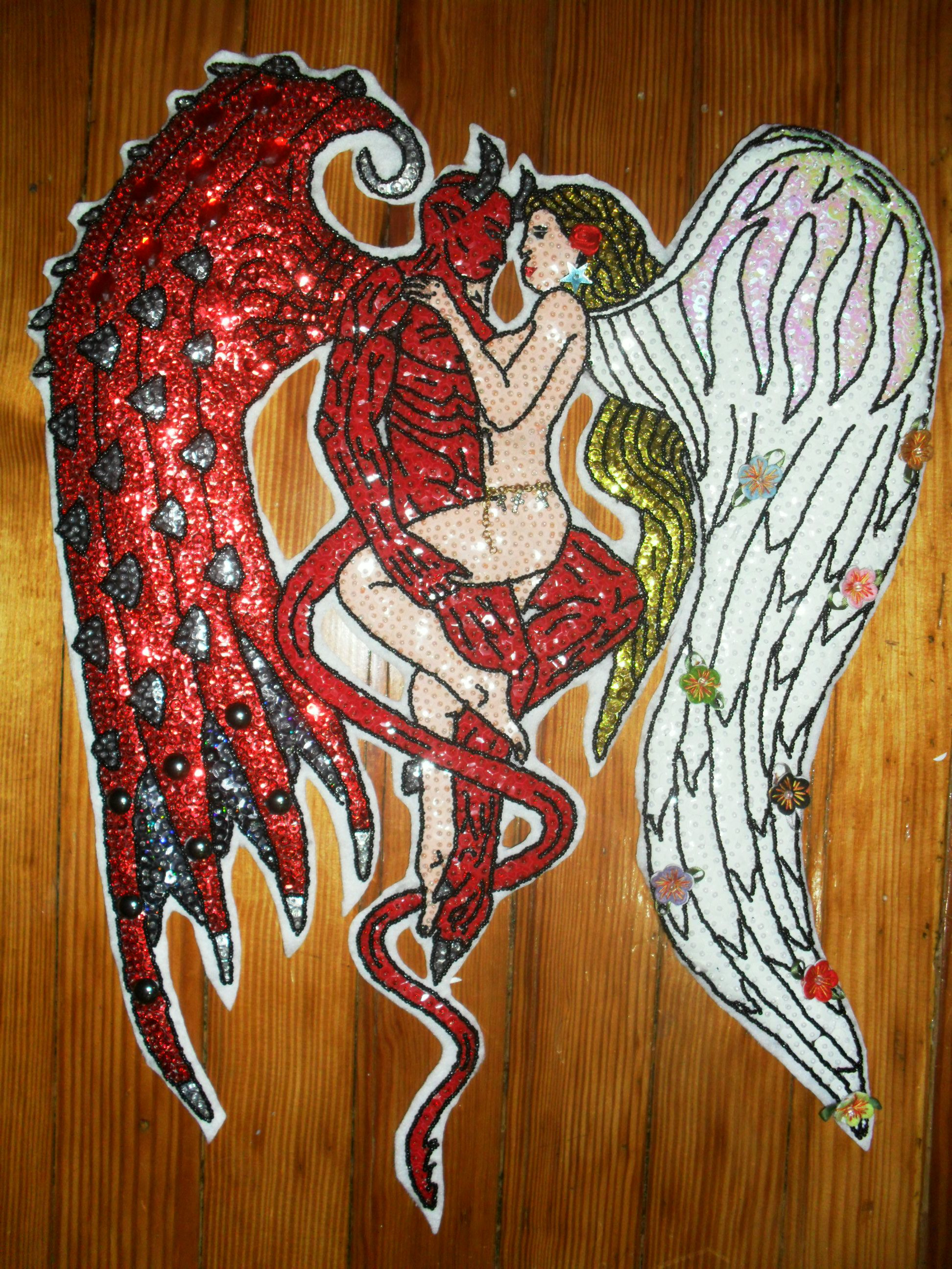 El Infierno y el Cielo se unierón para ser uno solo. Al dibujo original lo modifique, le cambie el ala al demonio y al ala del angel, los detalles de mlas flores, el caderin, las piedras, fuerón todos accesorios agregados, el color de lentejuela del ala y el demonio difieren quería que se notara, el mismo lo puse en un saco con el cual salgo comunmente a la calle, quien dijo que los bordados solo se pueden usar en Carnaval