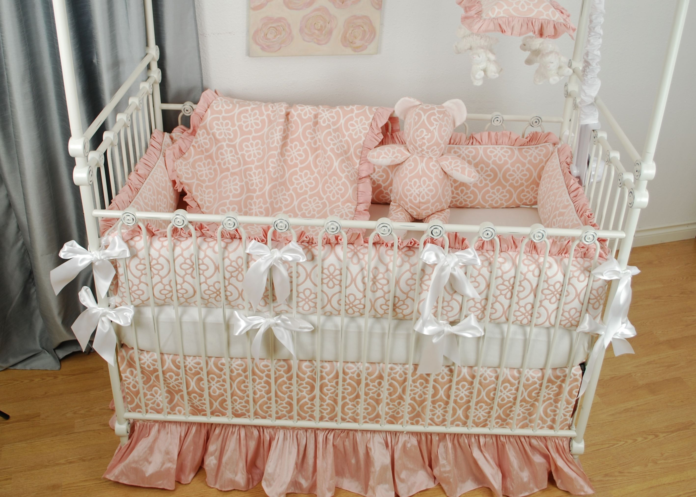 pink floral and silk crib bedding with white bows on a white bratt decor crib