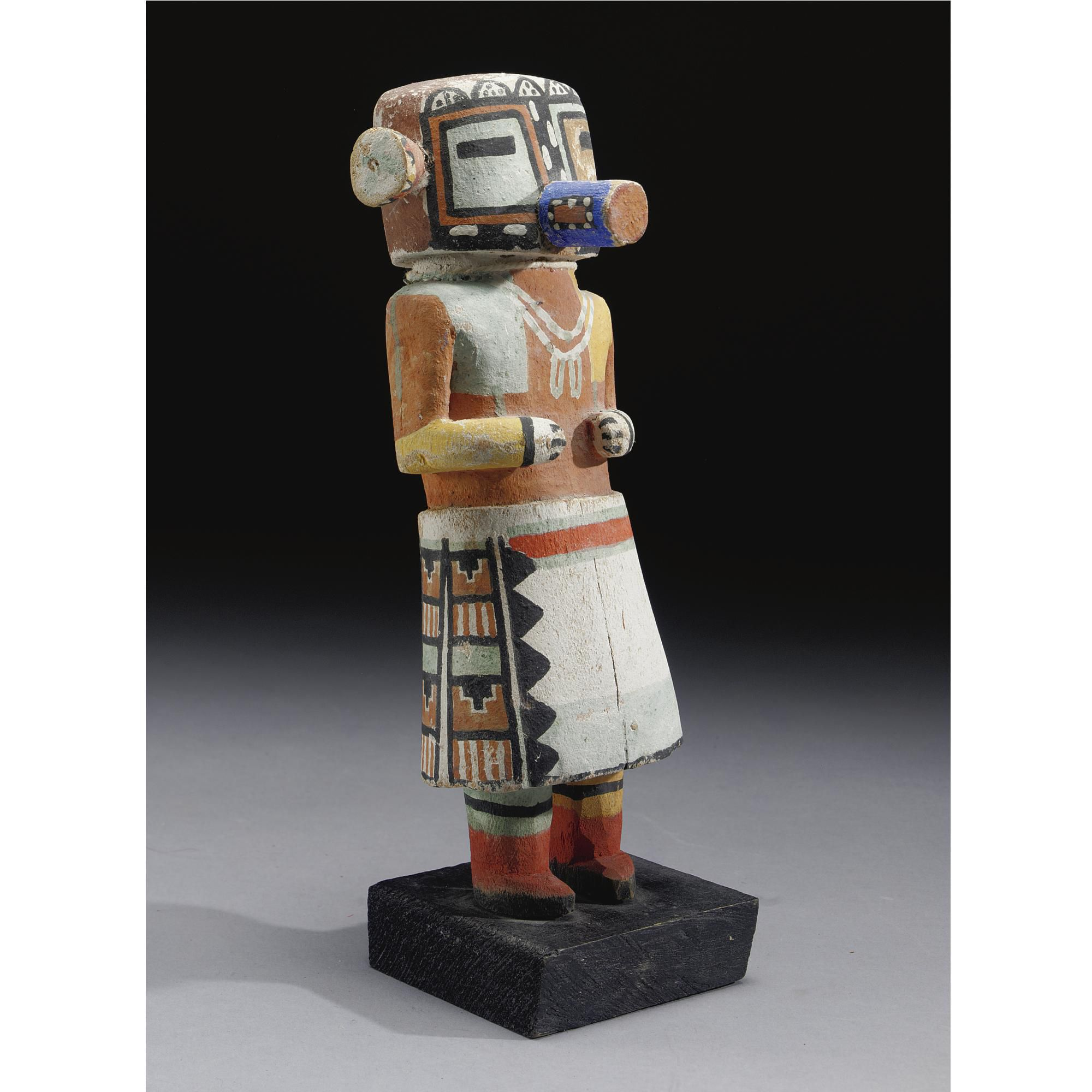 A HOPI POLYCHROMED WOOD KACHINA DOLL    composed of carved wood and pigments, depicting malo, with a blossom in place of the right ear.  Height without base 10 7/8 in.