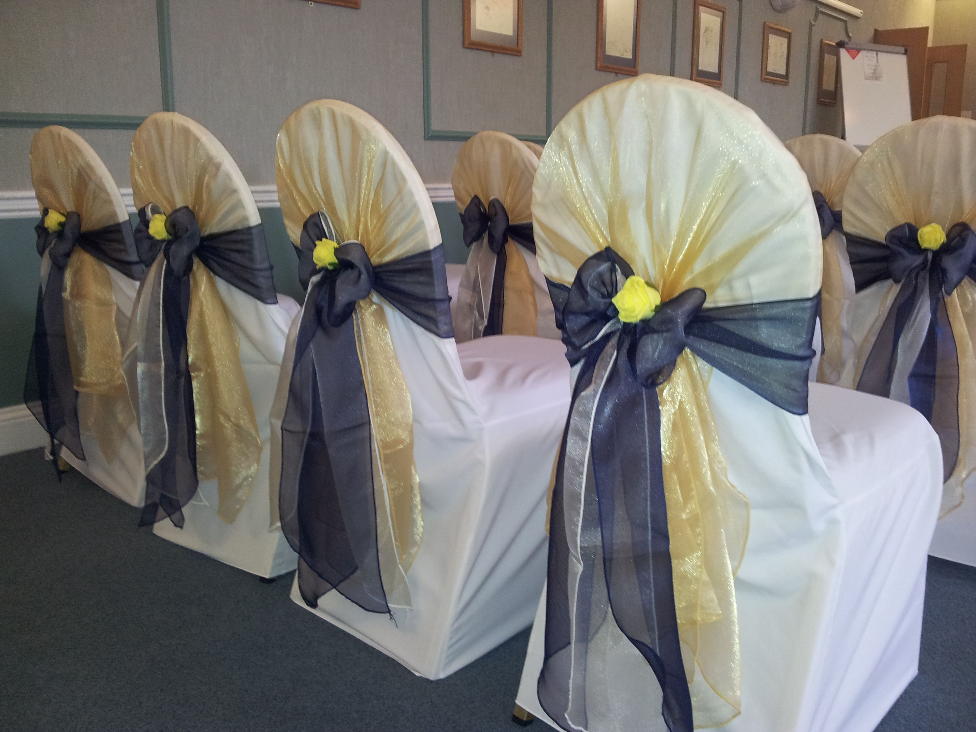 Gold Organza Shawl With Navy Organza Bows On White Chair Covers