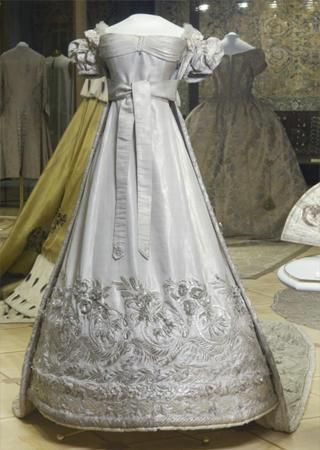 "Coronation Dress of Alexandra Feodorovna, born Princess Charlotte of Prussia: 1825, Russian. ""The silk-lined dress with a train is made of silver brocade...The item is of delicate forms, with a square cut of the bodices...The hem of the bell-shaped skirt is completed with a wadded roll and is embroidered with silver faceted threads. The long train...is executed in the form of a thrown open dress with a little bodice and pleats on the narrowed back."""