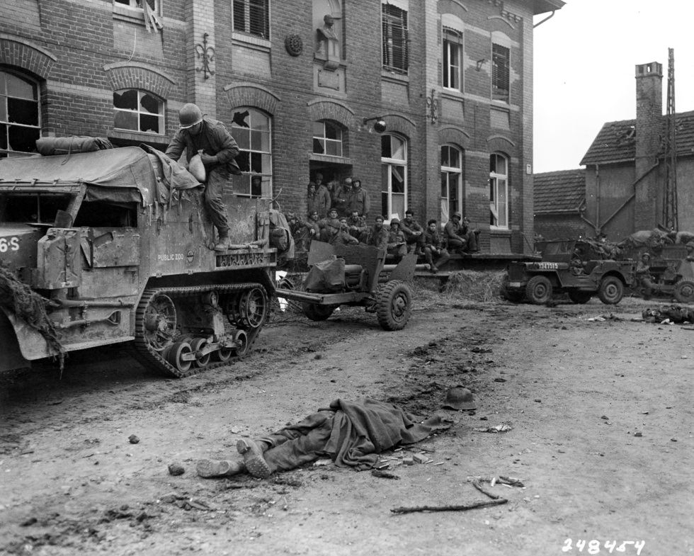 Troops of G Company and a 57 mm crew from AT Company rest after entering Vetweiss. The corpse in the foreground was one of the German defenders of the town.
