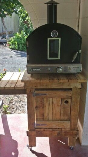 Home made pizza oven stand made out of old second hand pallets. Sanded and lightly stained for a natural look. Holds gas bottle in cabinet and room for two trays on side table. On castors for easy maneuverability. And only one and a half days of work.