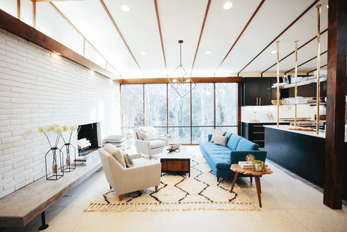 In the living room joanna redesigned the hearth and added modern concrete elements the fireplace brick was repaired and painted white to make a clean and