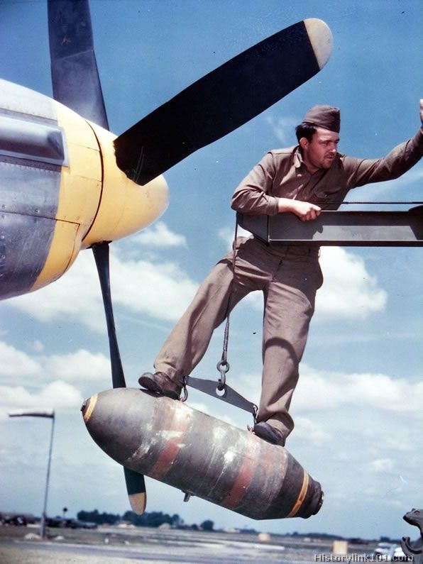 Cpl directs crane with a 500 lb bomb into place on the wing of a North American P-51 at a base in England.