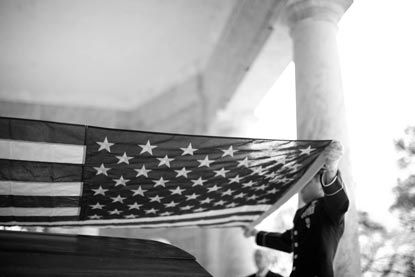 An honor guard folds an American flag over a veteran's casket.