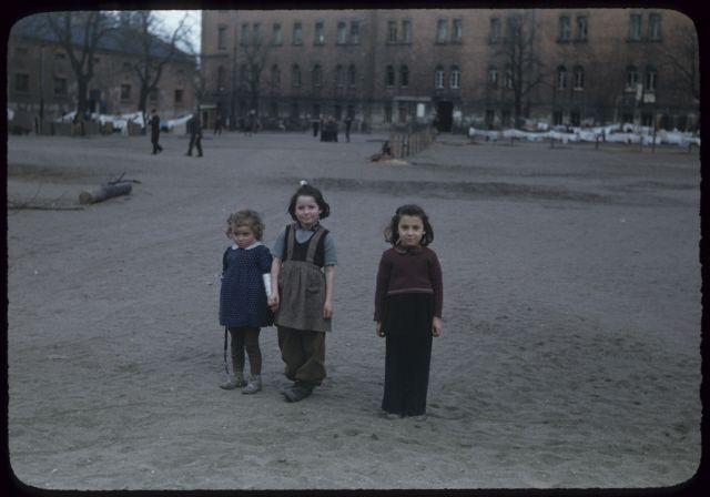 Three young girls pose at a displaced persons camp in Germany. 1947.