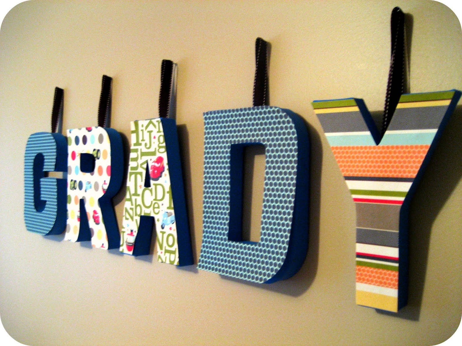 How to glue scrapbook paper to wood letters - Cover Wooden Letters With Scrapbook Paper And Modpodge Glue Attach Ribbons For Hangers And Have Unique Wall Art For Kids Room