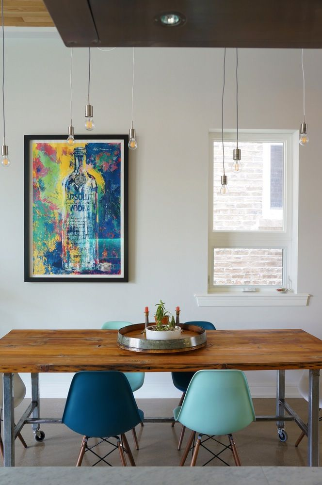 A white and wood dining room gets some life from colorful art and Eames shell chairs in shades of blue.