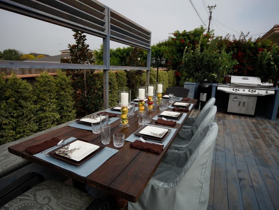 A long outdoor dining table offers generous seating for eight on this contemporary deck with a grill.