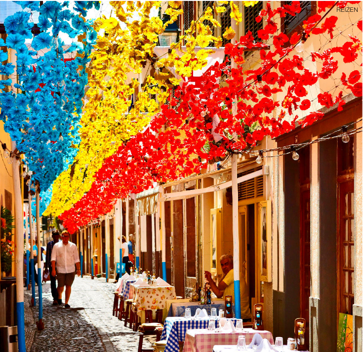Street decorated with paper flowers on feast of Madeira, Funchal old town