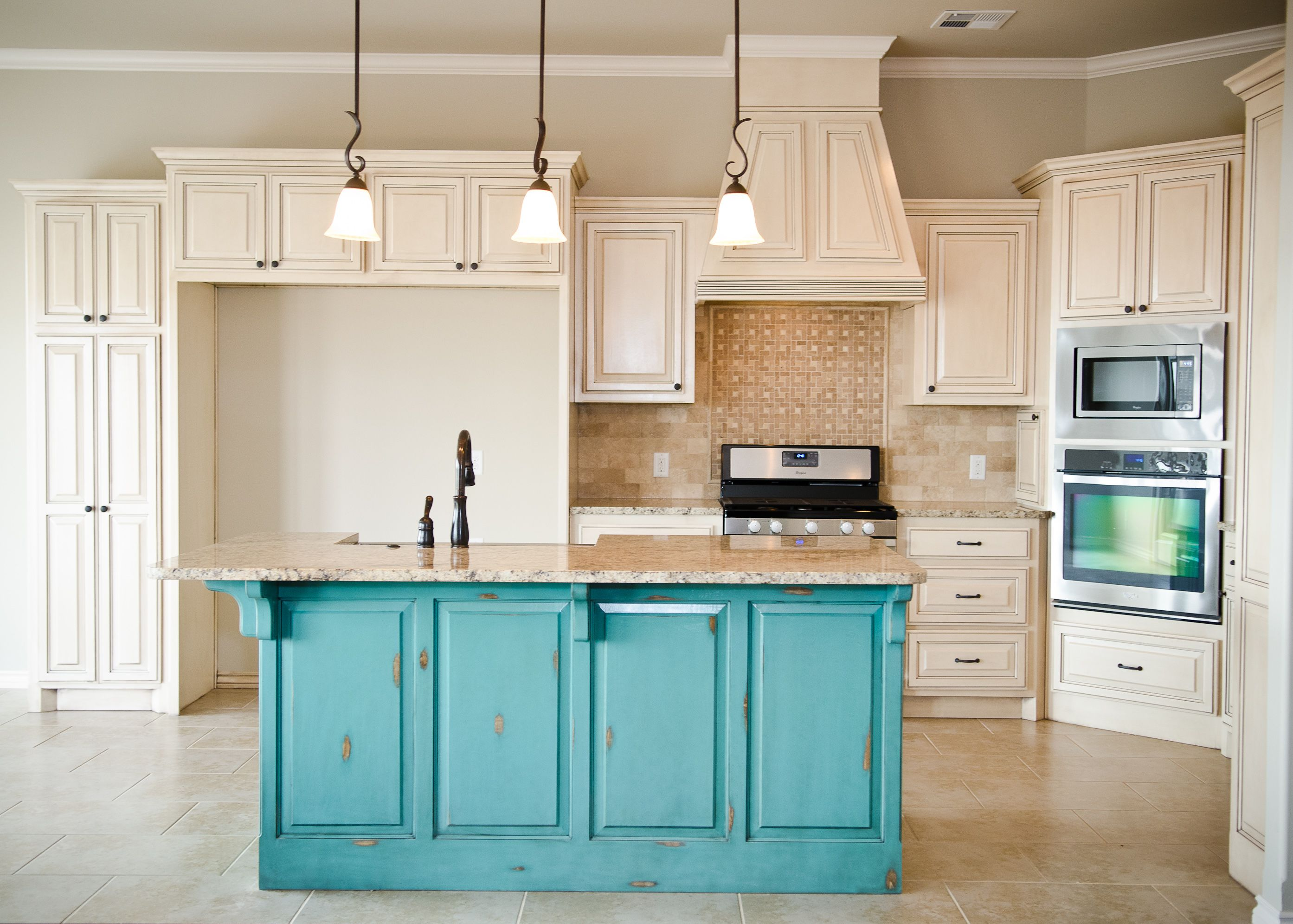 Distressed turquoise island with cream glazed cabinets for Cream kitchen cupboards