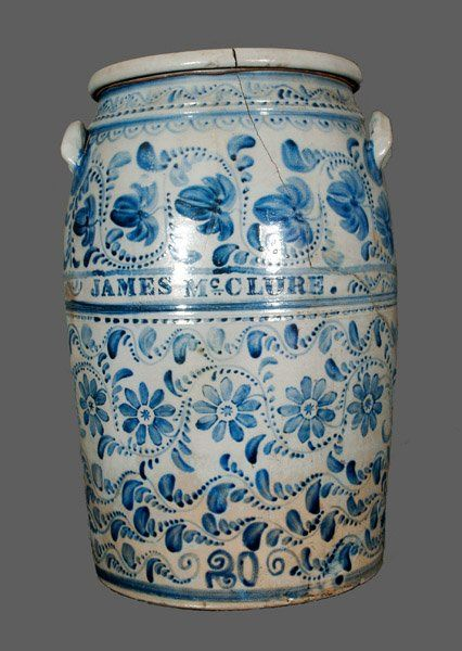 """Important Twenty-Gallon Stoneware Presentation Jar with Profuse Cobalt Freehand and Stenciled Decoration. Cylindrical jar with banded midsection, tooled shoulder, semi-squared rim, and applied lug handles. Front lavishly decorated with freehand vining, stripes, semi-lunate brushwork, and fuchsias, above the boldly stenciled name """"JAMES McCLURE"""" between two large bands of brushed cobalt slip. Reverse inscribed """"From James Hamilton & Co. / Greensboro, PA,"""" ca. 1875."""