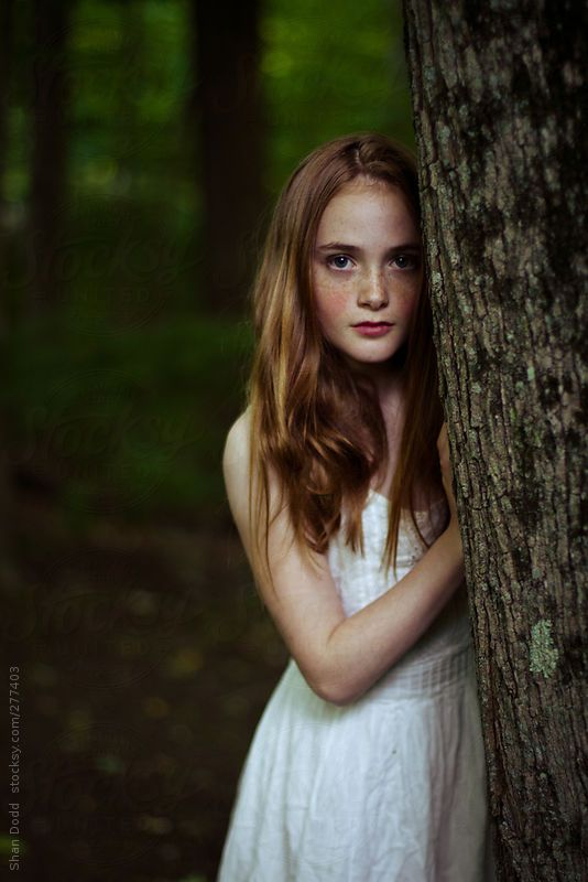 little red headed girl in woods by shan dodd - Stocksy United
