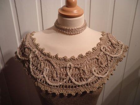 En strikket kjole inspirert av dronning Mauds kjoler.  Heklet bærestykke med påsydde rolourer i snirklete mønstre på heklet bærestykke.