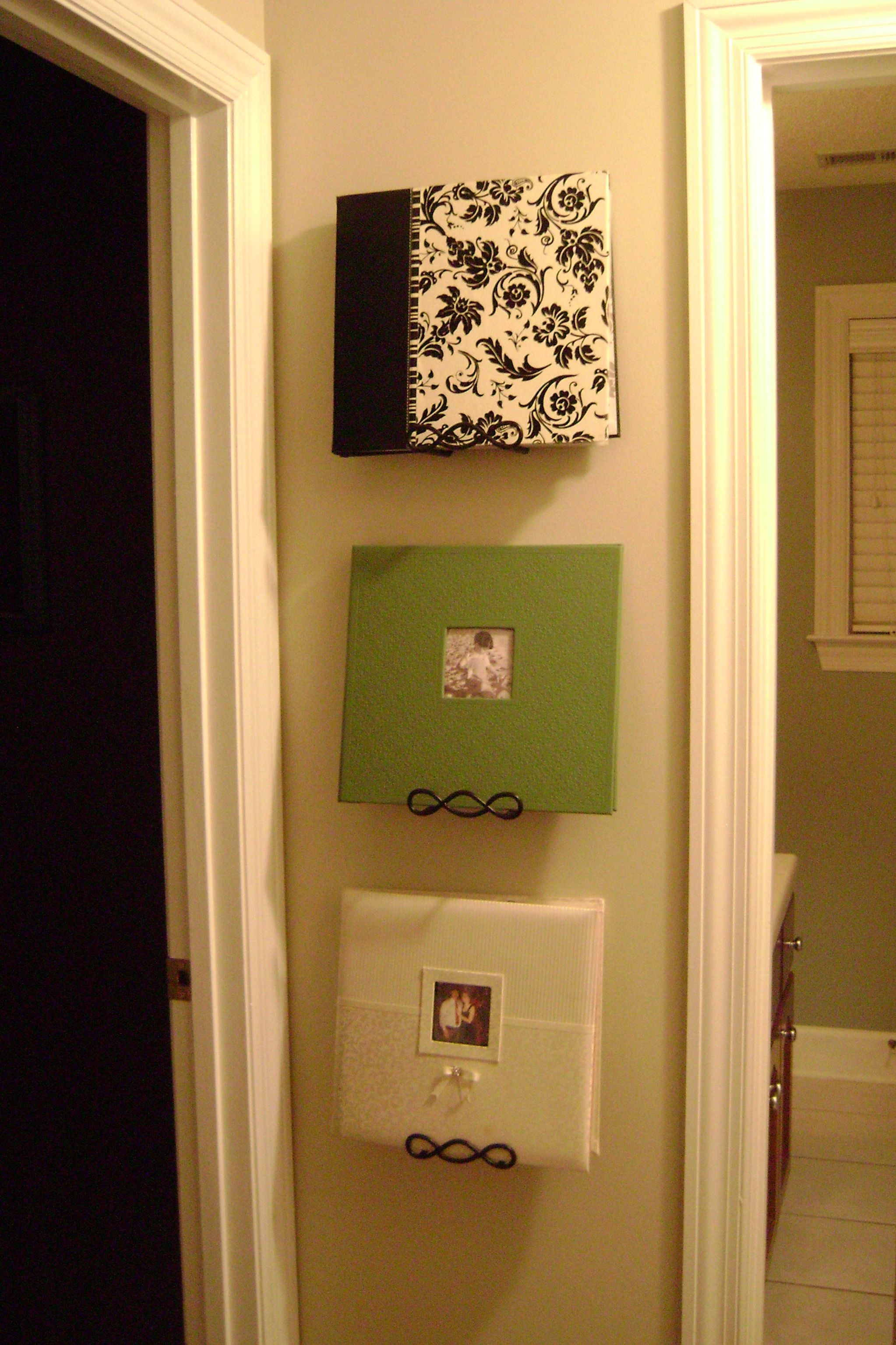 Scrapbooks on the wall using plate hangers...books and wall art ...